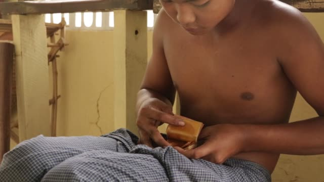 worker sorts thin strips of gold leaf in between sheets of bamboo paper at the king galon gold leaf workshop in mandalay, myanmar, on sunday, june 11... - gold leaf stock videos & royalty-free footage