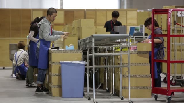 vidéos et rushes de a worker sorts various products onto shelves in a storage area as they wait to be packed at a distribution solution center inside japan post co's... - post it
