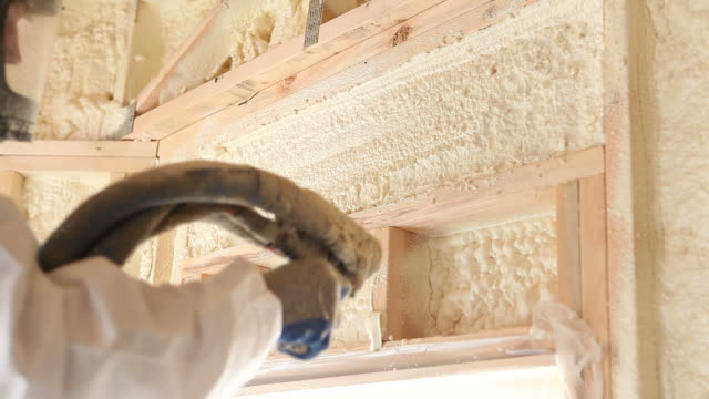 worker spraying expandable foam insulation between wall studs - insulator stock videos & royalty-free footage