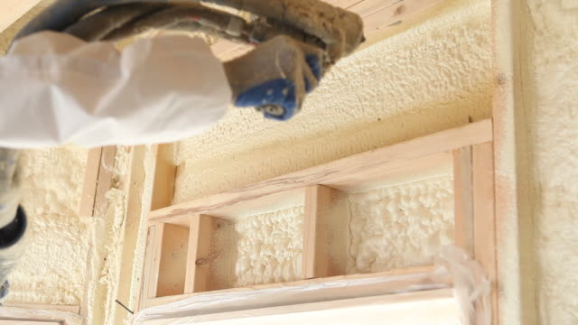 worker spraying expandable foam insulation between wall studs - spraying stock videos and b-roll footage