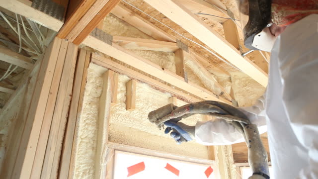 worker spraying expandable foam insulation on window header - spraying stock videos and b-roll footage