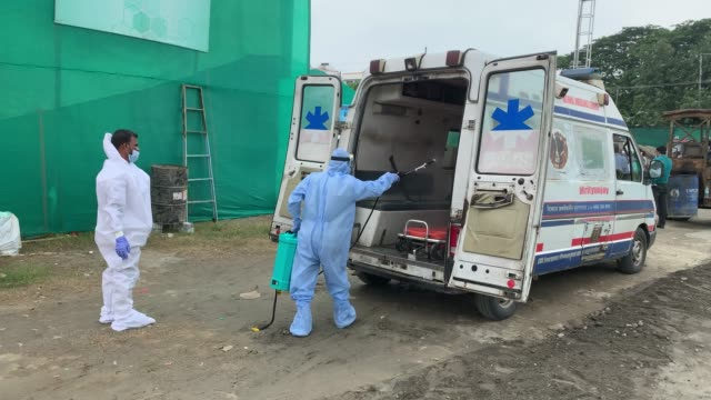 worker sprays disinfectant on an ambulance at a makeshift covid19 hospital at khanapara veterinary ground during the total lockdown imposed by the... - makeshift stock videos & royalty-free footage