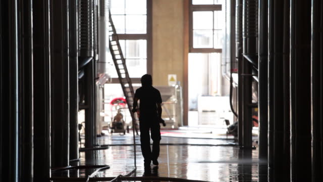 Worker sprays down floor at Septima winery