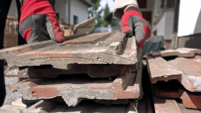 worker stacking roof tiles in sunshine - roof tile stock videos & royalty-free footage