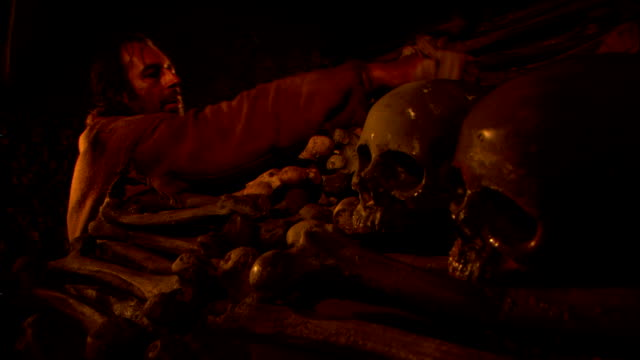 a worker stacks bones and skulls in an ossuary. - medieval reenactment stock videos & royalty-free footage