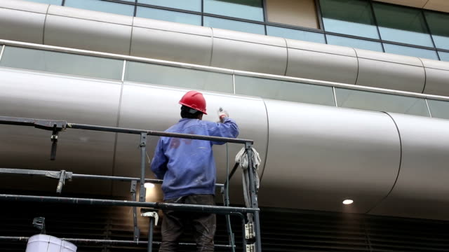 stockvideo's en b-roll-footage met worker stand on scaffold and painting building exterior - steiger bouwapparatuur