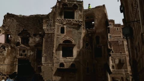 worker stand on the roof of one of the buildings of the historic old quarter of sana'a still standing as recent rains have threatened the city's... - unesco world heritage site点の映像素材/bロール