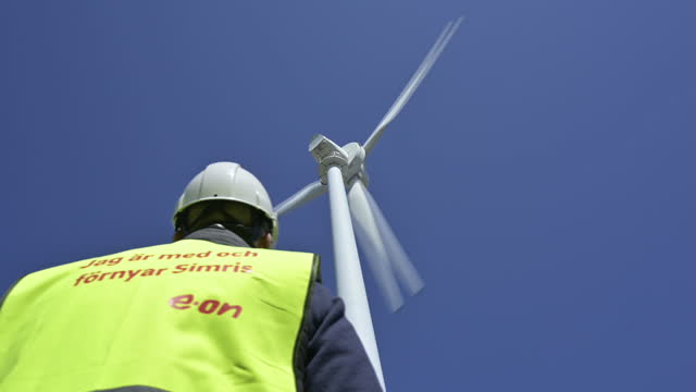 stockvideo's en b-roll-footage met worker standing below wind turbine producing energy in simrishamn, skåne län, sweden, on monday, april 19, 2021. simris have a micro-grid and use a... - low angle view
