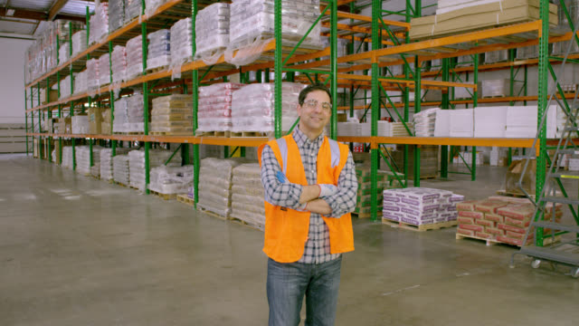 worker standing in warehouse smiling, looking to camera