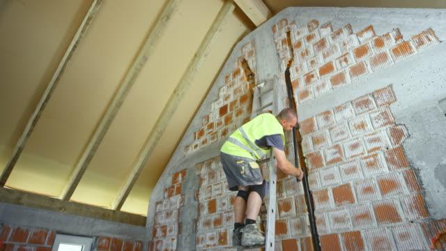 vidéos et rushes de travailleur permanent sur l'échelle et placer un tuyau dans le mur - échelle