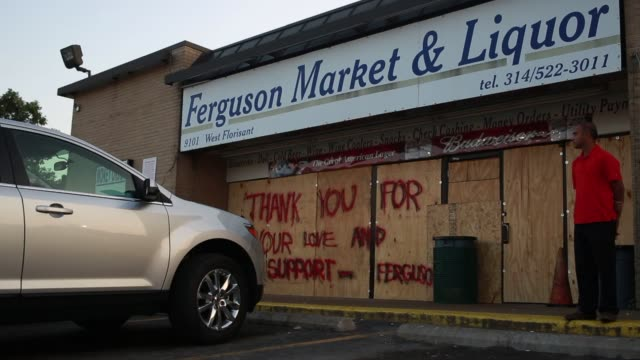 a worker stands in front of a ferguson market and liquor store which has been bordered and shuttered following demonstrations in ferguson missouri us - shutter stock videos & royalty-free footage
