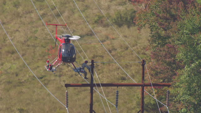 ws aerial pov worker strapped to helicopter checking power lines / merrimack county, new hampshire, united states - high up stock videos & royalty-free footage