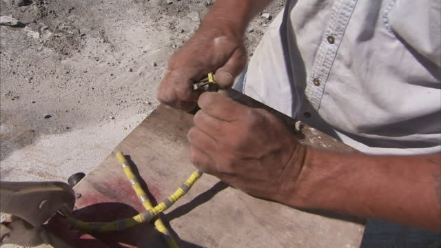 A worker strips a piece of wire and attaches a splice.