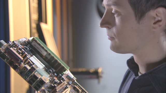 CU IT Worker studying computer motherboard and plugging expansion card into it/ Islandia, NY