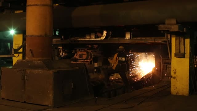 worker supervises the flow of hot liquid metal as it flows from a furnace during the smelting process at the nadezhda metallurgical plant, operated... - plant process stock videos & royalty-free footage