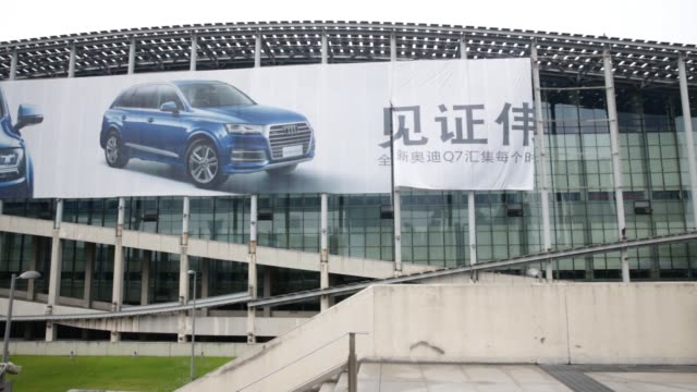 A worker suspended on a harness works on a large Audi Q7 advertising banner at the China Guangzhou International Automobile Exhibition in Guangzhou...