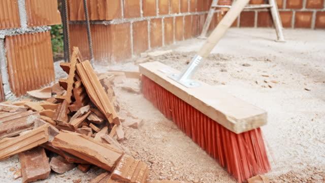 vídeos y material grabado en eventos de stock de slo mo trabajador barriendo el sitio de construcción - barrer