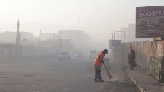 worker sweeps a street shrouded in haze in ulaanbaatar, mongolia, on tuesday, march 14 traffic drive past sacks of wood for sale, a vendor receives... - mongoliet bildbanksvideor och videomaterial från bakom kulisserna