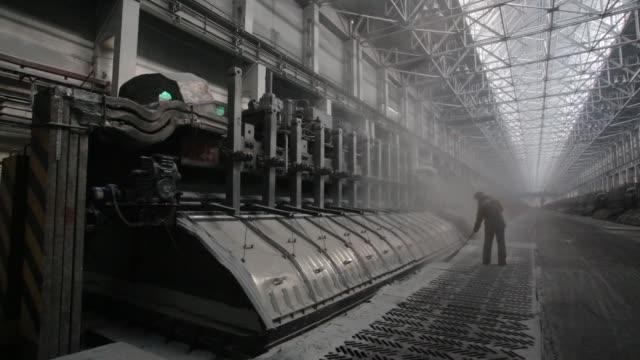 vídeos y material grabado en eventos de stock de worker sweeps the floor beside electrolysis baths in the electrolysis shop at the sayanogorsk aluminium smelter, operated by united co. rusal, in... - barrer