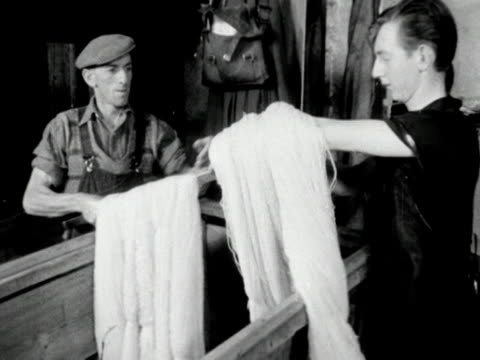 A worker takes skeins of wool off a conveyer belt at a wool mill