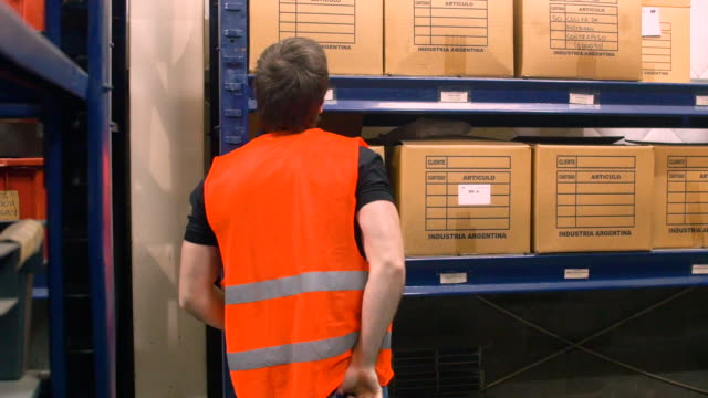 worker talking on walkie-talkie in warehouse - warehouse stock videos and b-roll footage