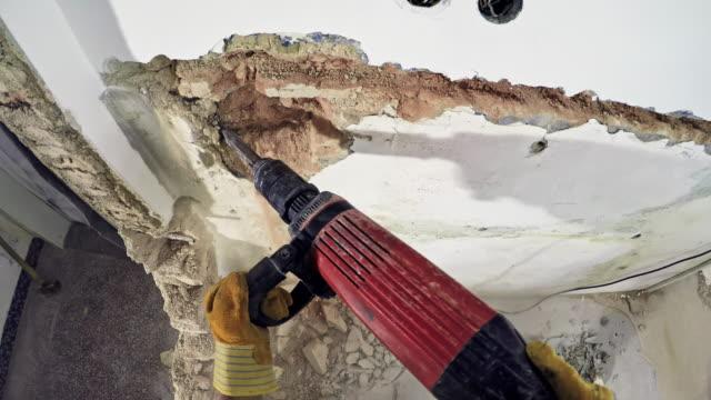 vídeos de stock, filmes e b-roll de trabalhador de pov, derrubando a parede de uma casa velha com uma britadeira - demolindo