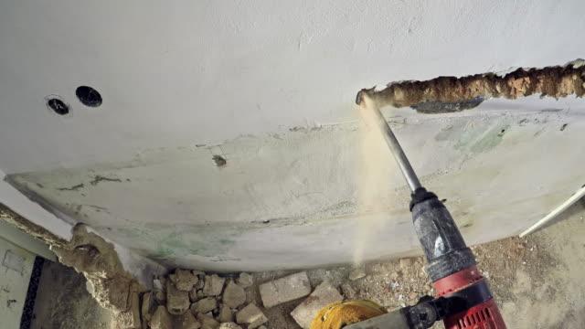 vídeos de stock, filmes e b-roll de trabalhador de pov derrubar uma parede com uma britadeira - demolido