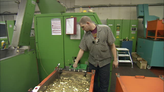 a  worker tests the quality of coins pouring from a minting machine. - geldmünze stock-videos und b-roll-filmmaterial