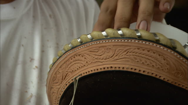 a worker threads a needle through a strip of  tooled leather. - belt stock videos & royalty-free footage