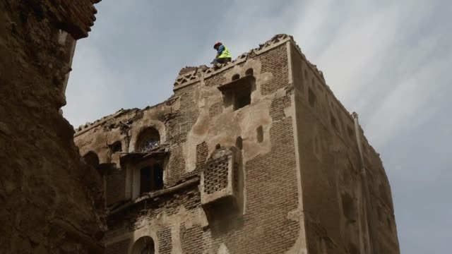 worker throws debris and bricks from the top of the buildings of the historic old quarter of sana'a stand as recent rains have threatened the city's... - unesco world heritage site点の映像素材/bロール