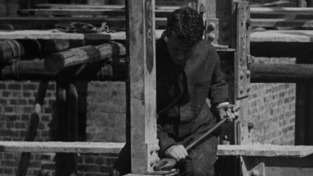1930 ms worker tightening bolts on girders before walking along one / united kingdom - wrench stock videos & royalty-free footage