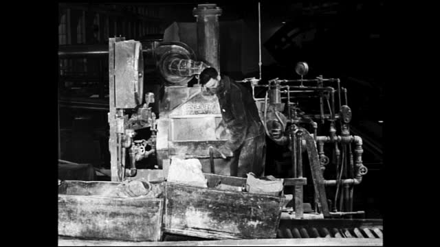 worker tossing supplies from the metal bin into machine and taking them out inside factory - 1940 1949 stock videos & royalty-free footage
