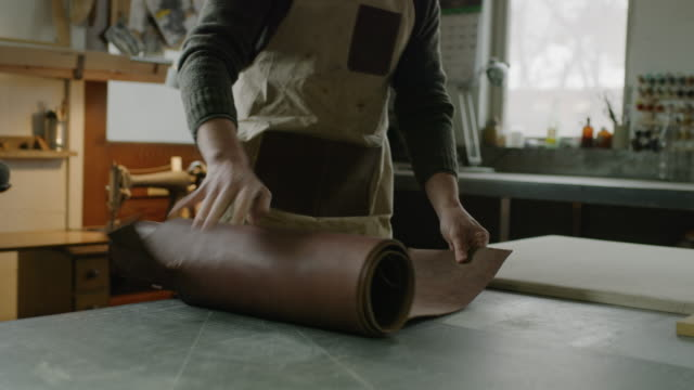 worker unrolling leather then adjusting tool in workshop / provo, utah, united states - cucire video stock e b–roll