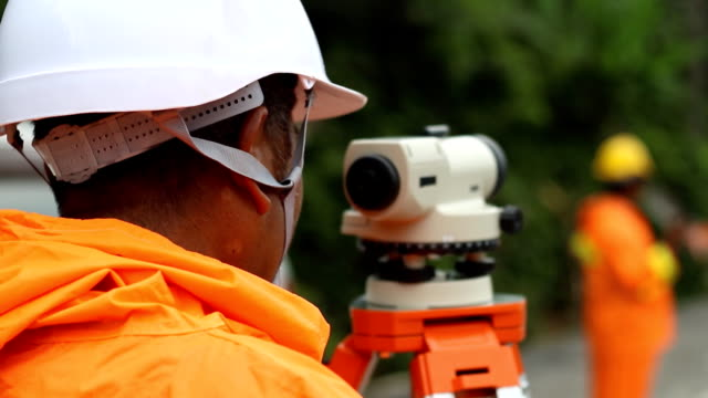 worker use surveyor's telescope at new road construction site