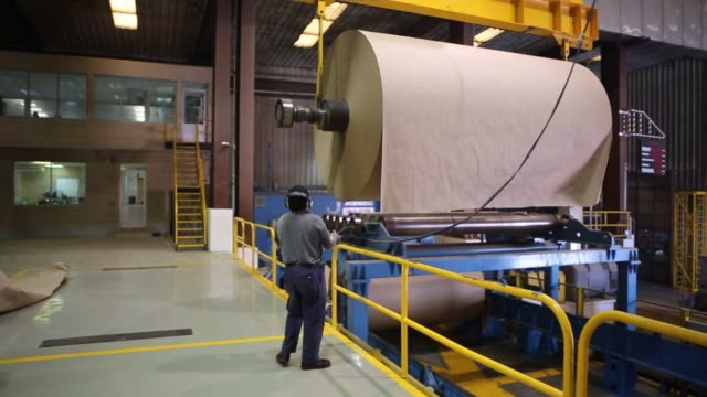 worker uses a crane to move a roll of kraft paper out of the paper mill and into the cutting machine employee works on a roll of kraft paper in the...