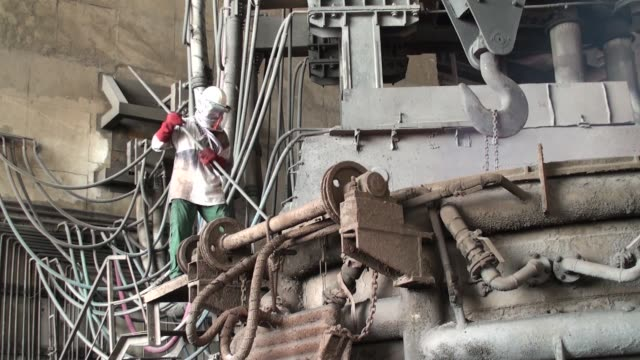 stockvideo's en b-roll-footage met a worker uses a hammer and nail on a large metal cylinder in a pile at a scrapyard inside an agha steel industries ltd plant in karachi pakistan on... - soeplepel