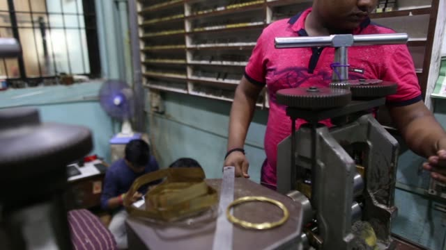 A worker uses a machine to create gold strips at a PN Gadgil Jewellers Pvt workshop in Pune India on Monday Aug 17 Close up a worker pulls out a gold...