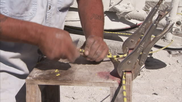 A worker uses a razor blade to strip the end of a piece of wire.