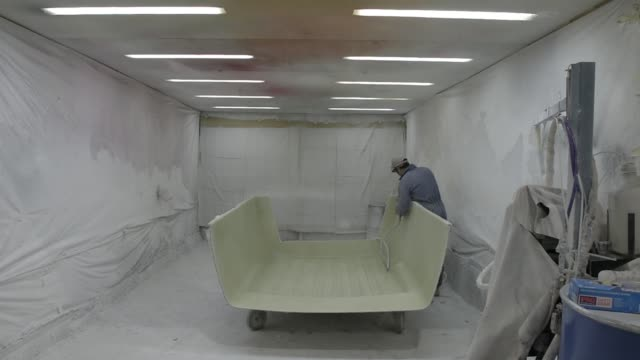 a worker uses a roller to smooth out the resin and fiberglass of a part at a king's fibreglass pty ltd facility in melbourne australia on wednesday... - fibreglass stock videos and b-roll footage