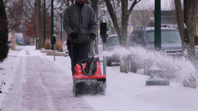A worker uses a snow plow to clear snow from a sidewalk in Bloomington Indiana