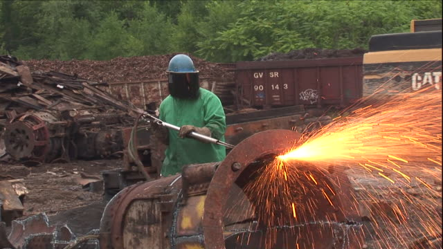 a worker uses a welding torch to cut a scrap metal pipe. - welding helmet stock videos & royalty-free footage