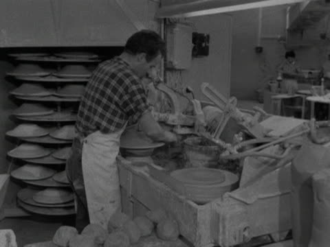 worker uses an automatic wheel to shape and form, shallow clay bowls at the stavanger pottery workshop. 1959. - stavanger stock videos & royalty-free footage