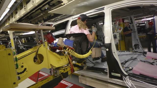 vídeos de stock e filmes b-roll de ms pan worker uses an ergonomically designed sled to help her move inside mini-van as she installs accessories / princeton, indiana, united states - fábrica de automóveis