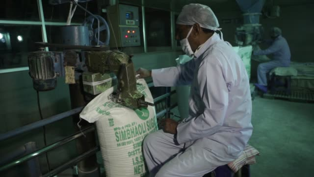 A worker uses machinery to seal 50 kilogram sacks of sugar in the packaging unit of the Simbhaoli Sugars Ltd mill in Ghaziabad Uttar Pradesh A worker...