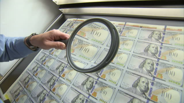 ms worker uses magnifying lens to inspect sheet of one hundred dollar bills / washington d.c., washington d.c., united states - magnifying glass stock videos & royalty-free footage