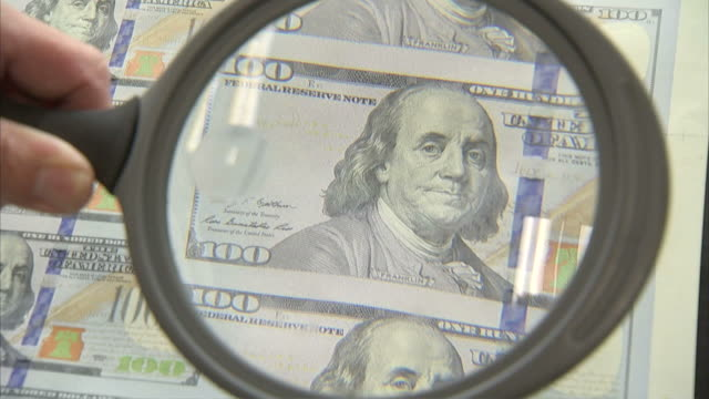 cu zo worker uses magnifying lens to inspect sheet of one hundred dollar bills / washington d.c., washington d.c., united states - benjamin franklin stock videos and b-roll footage