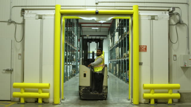 Worker using a forklift in a warehouse