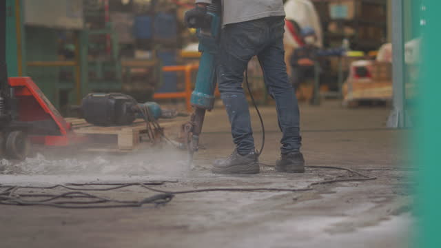 vídeos de stock, filmes e b-roll de trabalhador usando uma britadeira cortando o chão de concreto, perfurando o piso de concreto para reparo, trabalhar duro desmontando a construção na fábrica - pista asfaltada