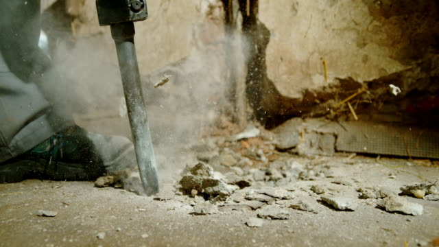 slo mo worker using a jackhammer for chopping away the concrete floor - chisel stock videos and b-roll footage