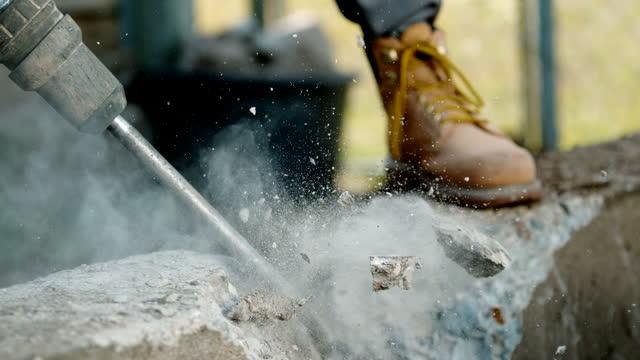 vídeos y material grabado en eventos de stock de super slo mo worker usando un martillo para romper el bloque de hormigón - herramienta de mano